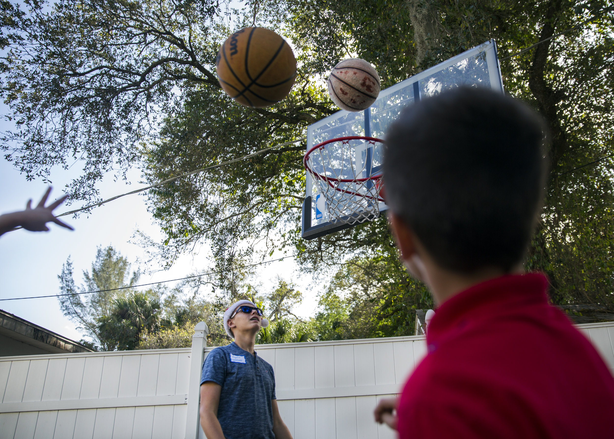 Kids take turns throwing the basketball as Wyatt Sargent, a volunteer, rebounds during the first holiday party at Valerie's House in Fort Myers on Saturday, December 17, 2016.