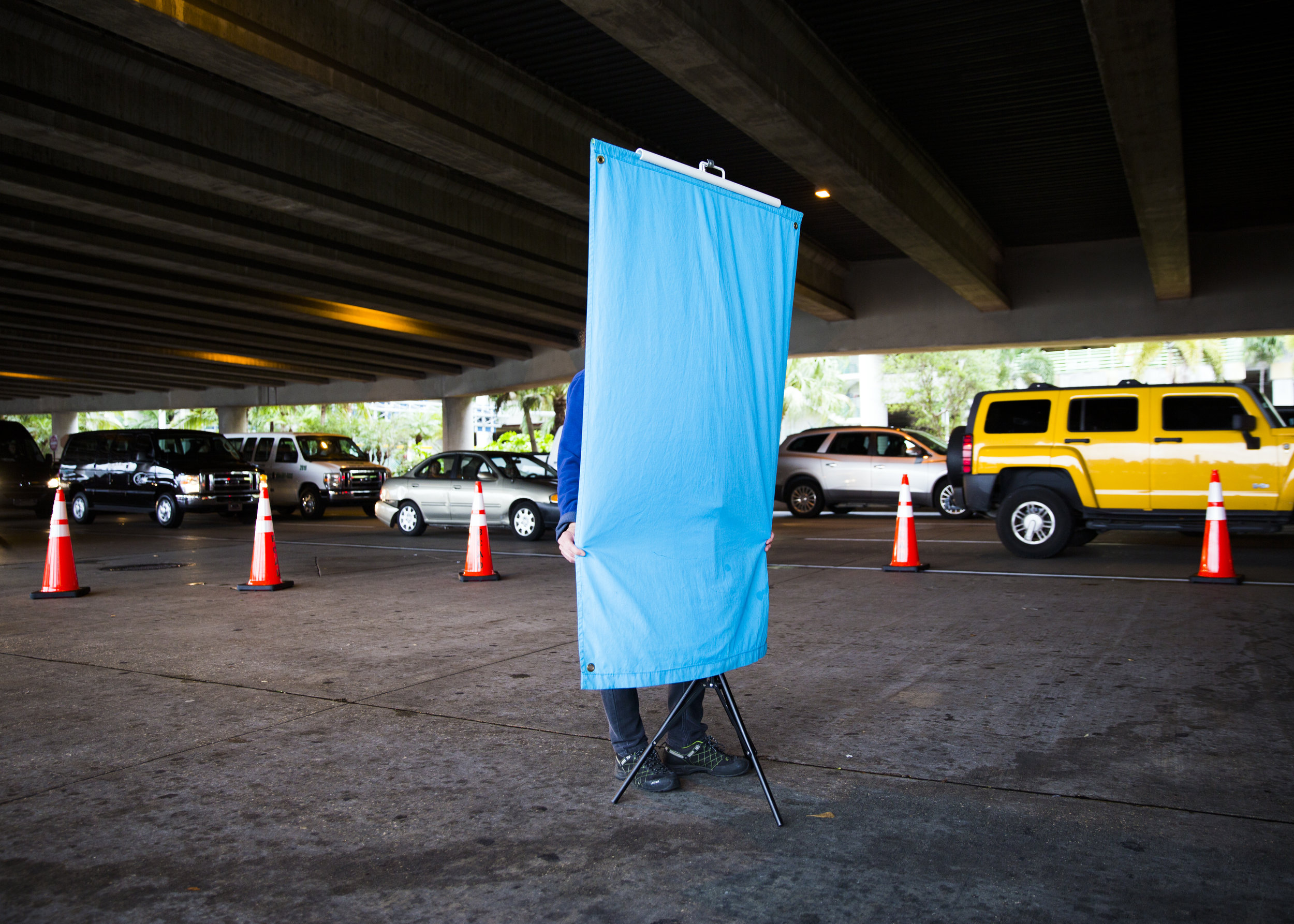 A worker with Florida Licensing on Wheels holds a backdrop taught for identification photos between the baggage claims for terminals one and two at the Fort Lauderdale - Hollywood International Airport in Fort Lauderdale, Fla. on Saturday, January 7, 2017. A Safer Florida and Florida Licensing on Wheels arrived at the airport late afternoon to help those who lost their drivers license as a result of the shooting get a form of identification.