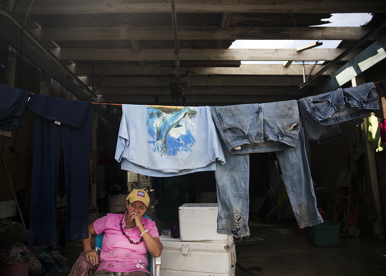 "Crystal Holler waits for her clothes to dry in the garage of her neighbor's home in Chokoloskee on Wednesday, September 13, 2017, three days after Hurricane Irma. ""All of my clothes came flying out of the house,"" said Holler. She returned home to find her clothing covered in mud in her yard."