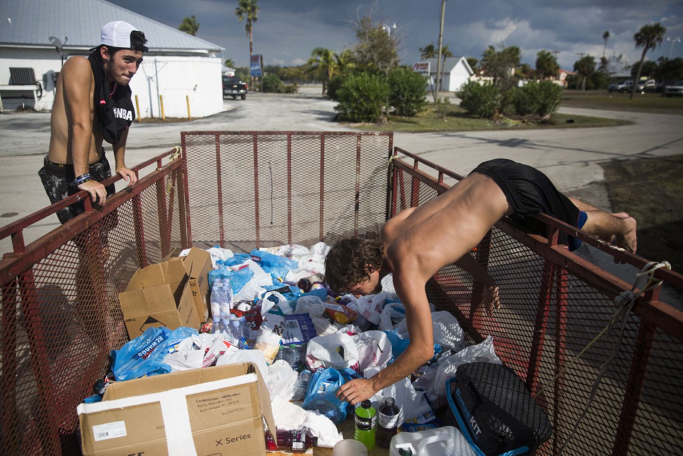 Brandon Beaty, left, looks around at the supplies as Devin Daniels, 23, reaches into a trailer of supplies for Powerade at Fire Station 60 on Wednesday, September 13, 2017 in Everglades City, three days after Hurricane Irma.