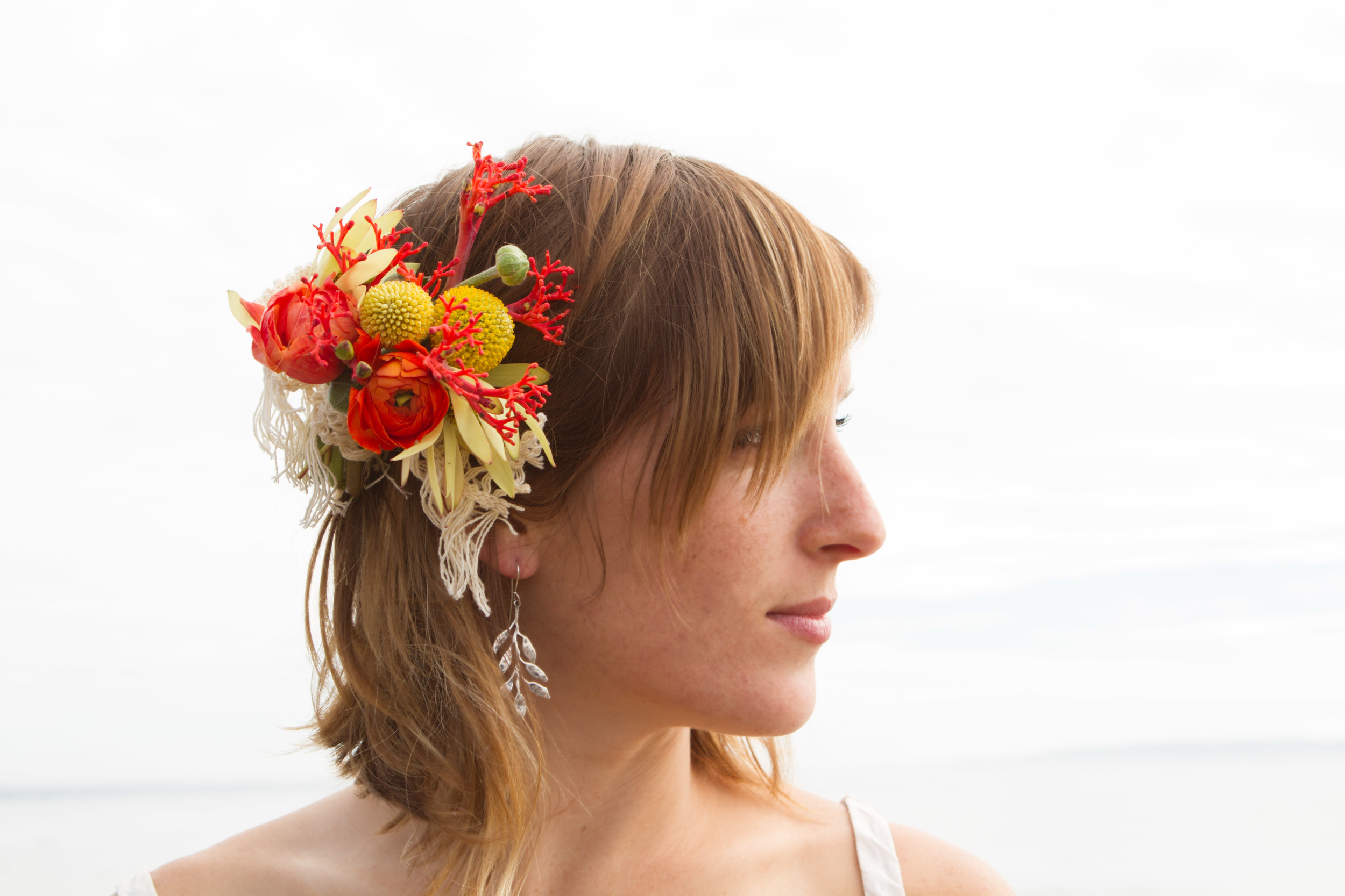 Faith Dickey modeling a floral hairpiece featuring orange ranunculus, coral flower and a few other choice picks. Photo: J.R. Racine.