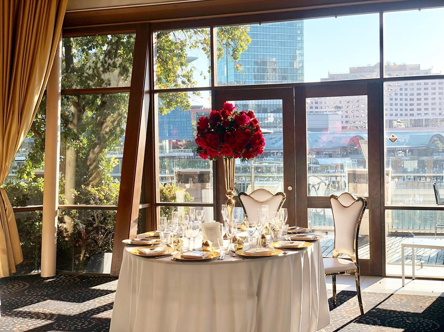 red floral centerpieces in gold vases.jpg