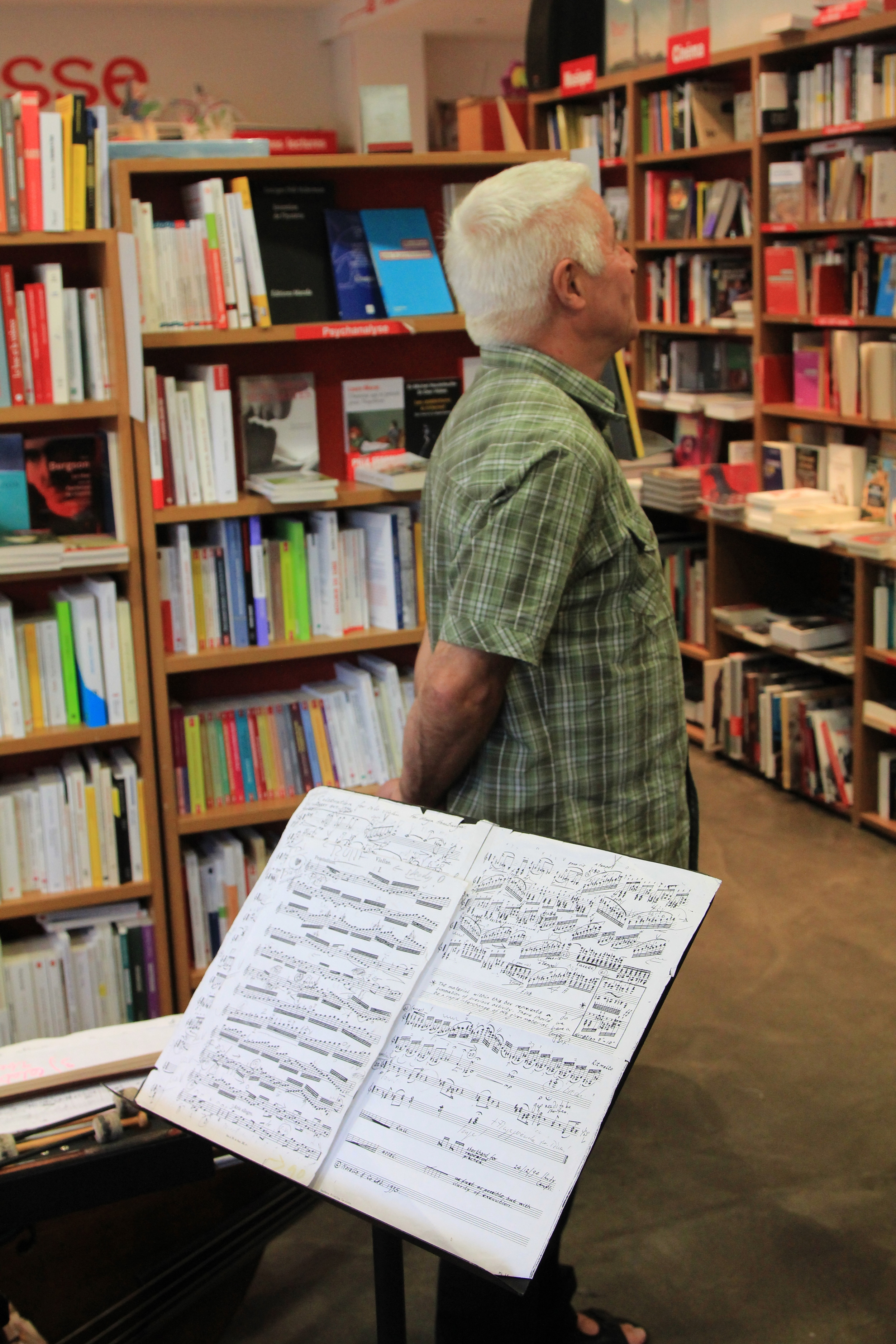 Barry Guy surveys the shelves at Le comptoir des mots prior to his performance with Maya Homburger. Photo: Dan Gunn.