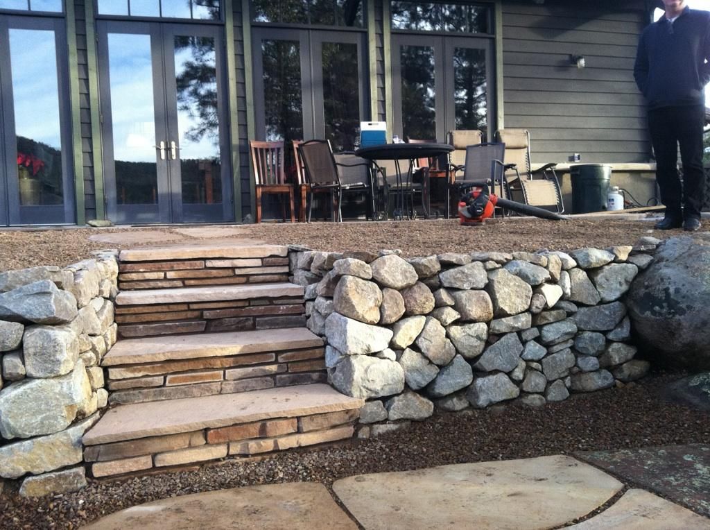 Dry stacked granite retaining wall with flagstone steps.