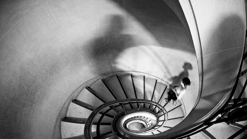 A woman ascends a spiral staircase in Paris.
