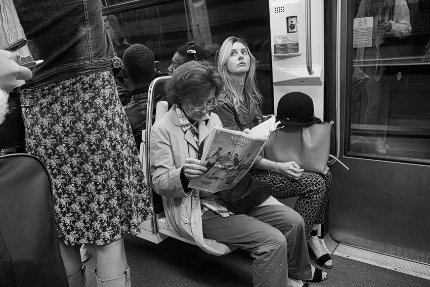 A woman on the Paris Metro checks out another's fashion.