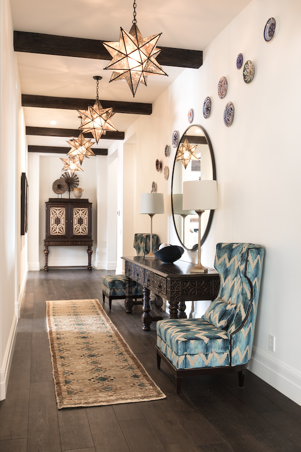 Hilltop Hacienda is an interior design project by Denise Morrison Interiors featuring a hallway with large start pendants.
