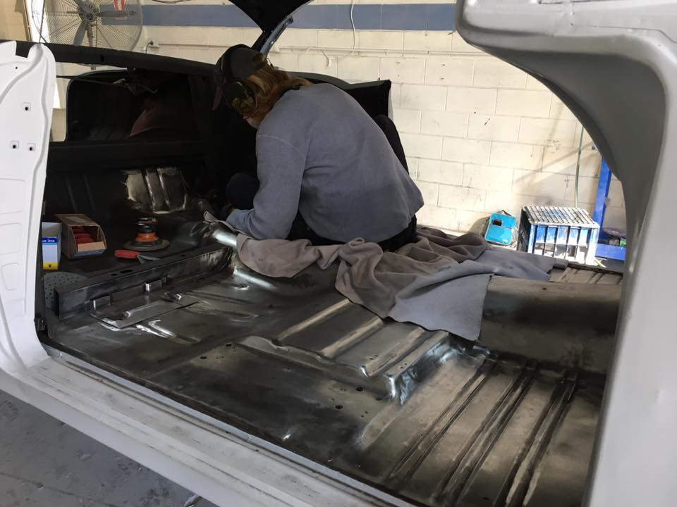 Henry grinds the factory etch primer of the new floor in my '55 Chev ready for a protective coat of epoxy primer.