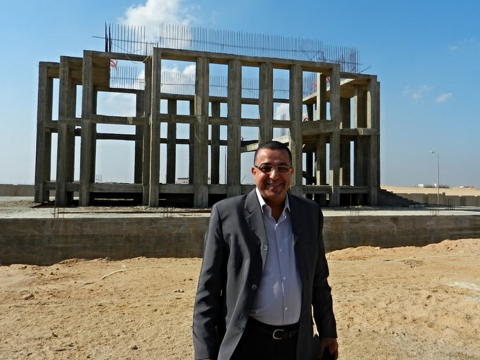 Rev. Awni Salib with construction skeleton behind him