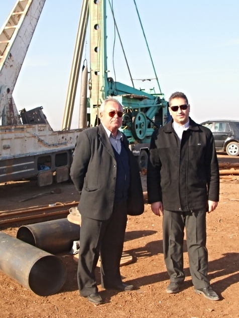 Rev. Feras (rt) awaits the positioning of the drill rig with one of his elders