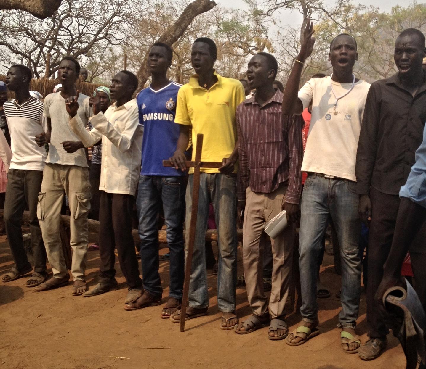 Older youth in refugee camp praising God in loud, fervent song.