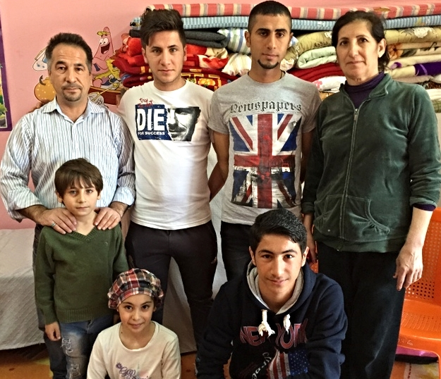"""This Syrian Orthodox family from the Nineveh Plain is grateful for their new """"home"""" in a 12' x 30' Sunday School room at the Kirkuk church. It holds everything they now own."""