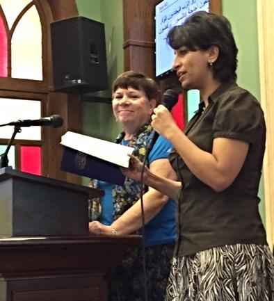 Rev. Deena Candler preaching with Professor Anne Zaki translating