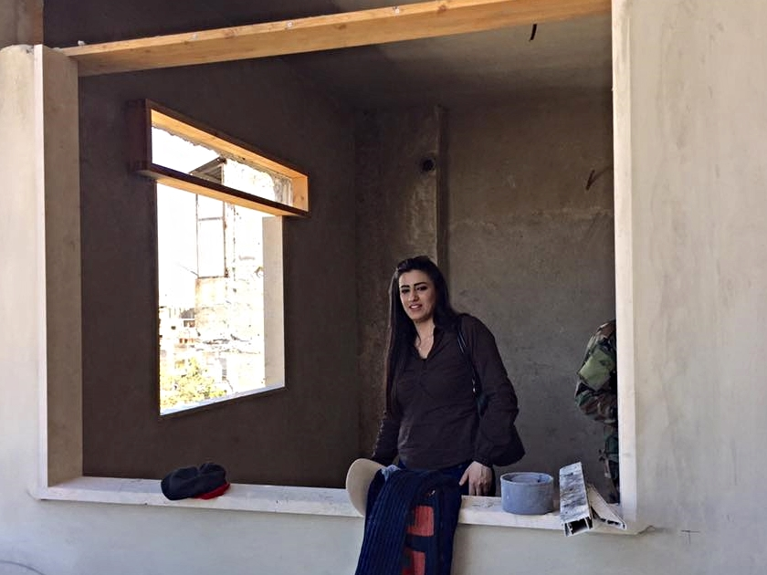 Michelline Koudmani, wife of pastor Mofid from Homs, standing in her aunt Mona's apartment which is currently under restoration.