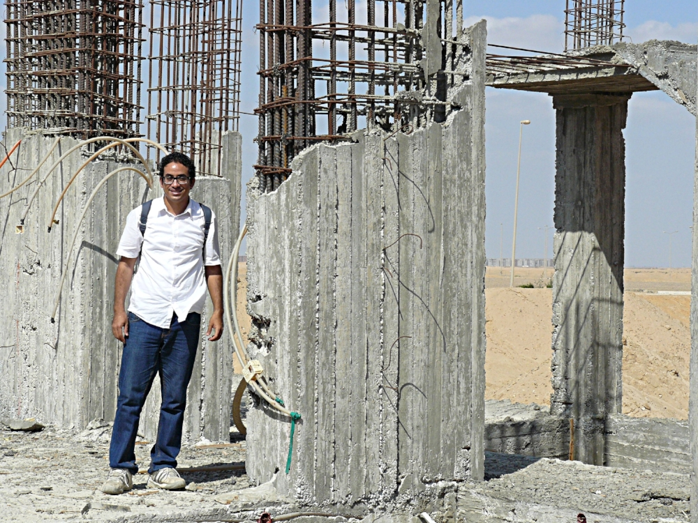 """Amir"" standing in the new church, awaiting funds to continue construction ."