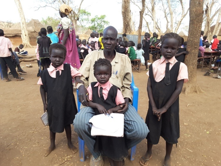 Refugee and now teacher John Yien Pual shown with his children Nyaboth, Nyaduoth, and Nyabhan