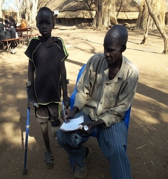 Kuey Tot receives help with his school work from teacher John Yien Paul