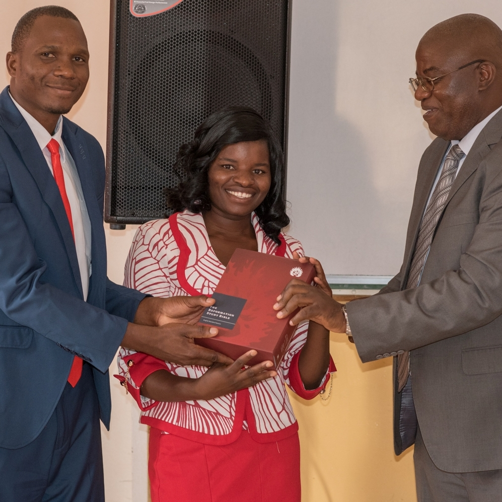 Naele Mawere (center) being presented a study Bible by Prof. Edwin Zulu and fellow student Abraham Phiri.
