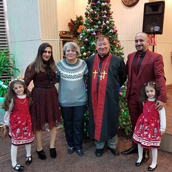 Mayada (in blue sweater) and Rev. Haitham with a church family this past Christmas.
