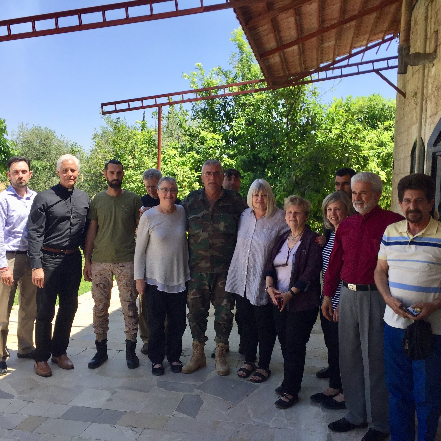 Gen. Simon of the Mahardeh defense unit surrounded by Outreach team, Rev. Ma'an is second from the right