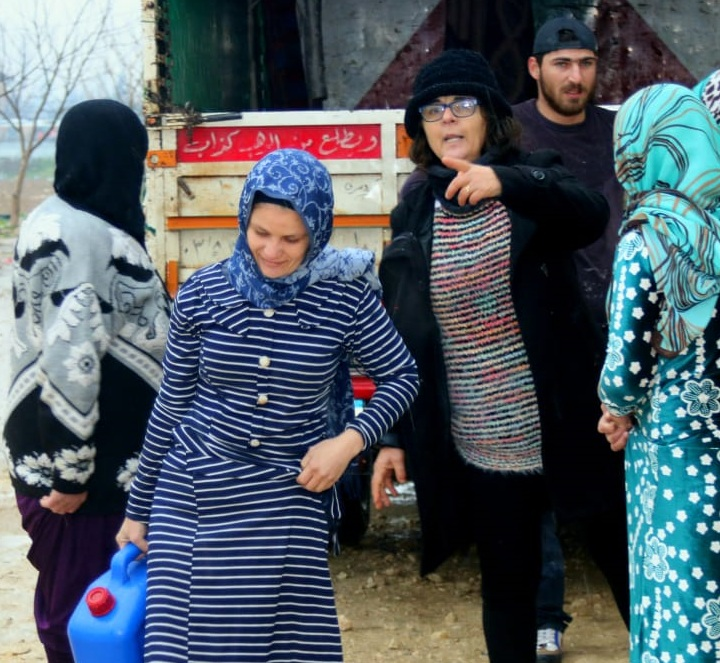 Refugee IDP Appeal January 2019 Izdihar (in black) delivers heating fuel.png