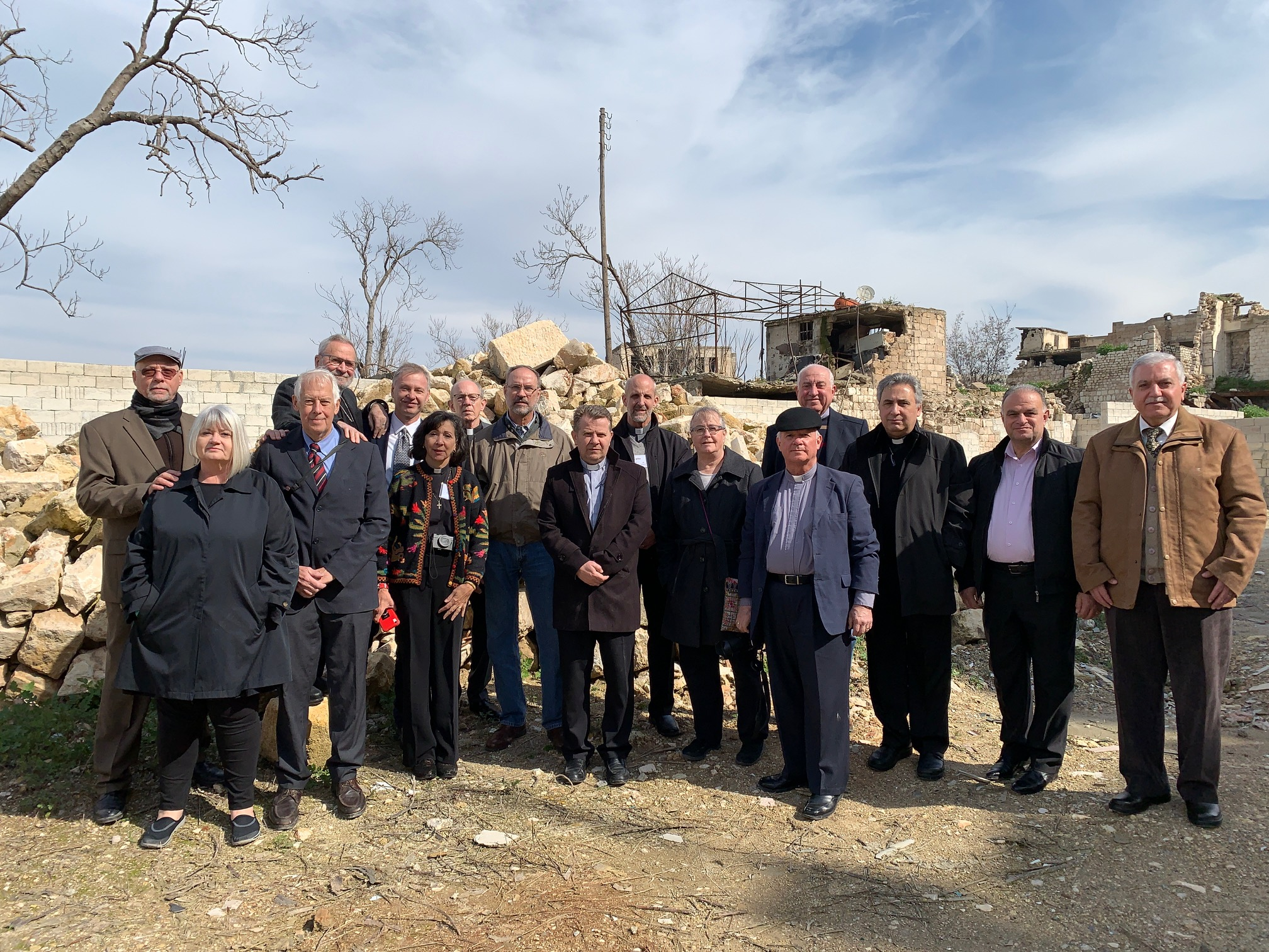 Outreach team with Rev. Nseir and elders of the Aleppo church standing in the rubble of the original church destroyed in November, 2012