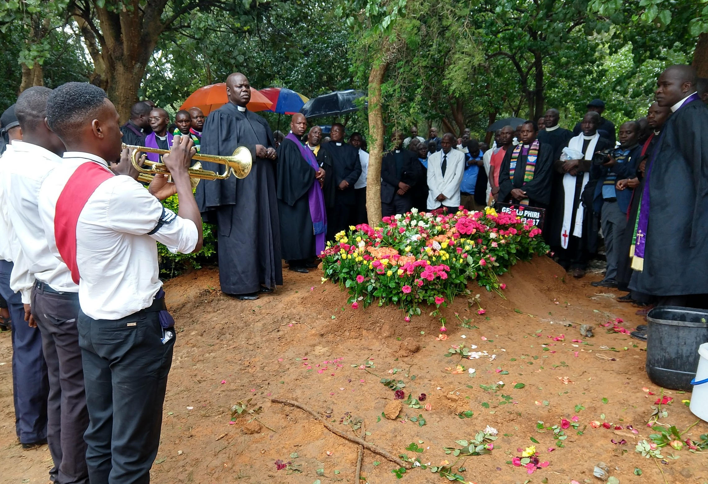 Final goodbye for Rev. Gerald Phiri. A tradition is for friends and loved ones to insert flowers into the earth covering the grave.