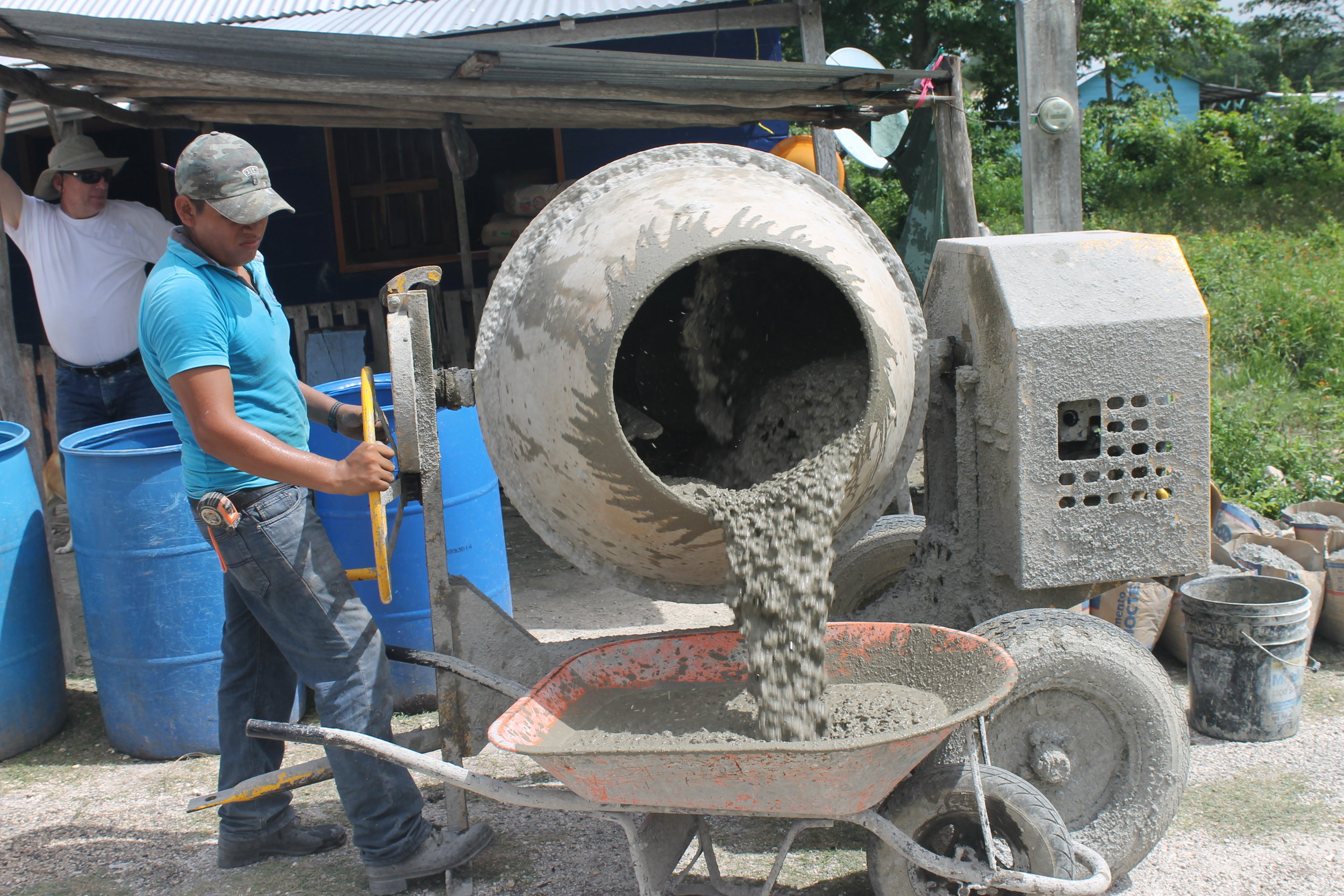 Isaias operating the concrete mixer.