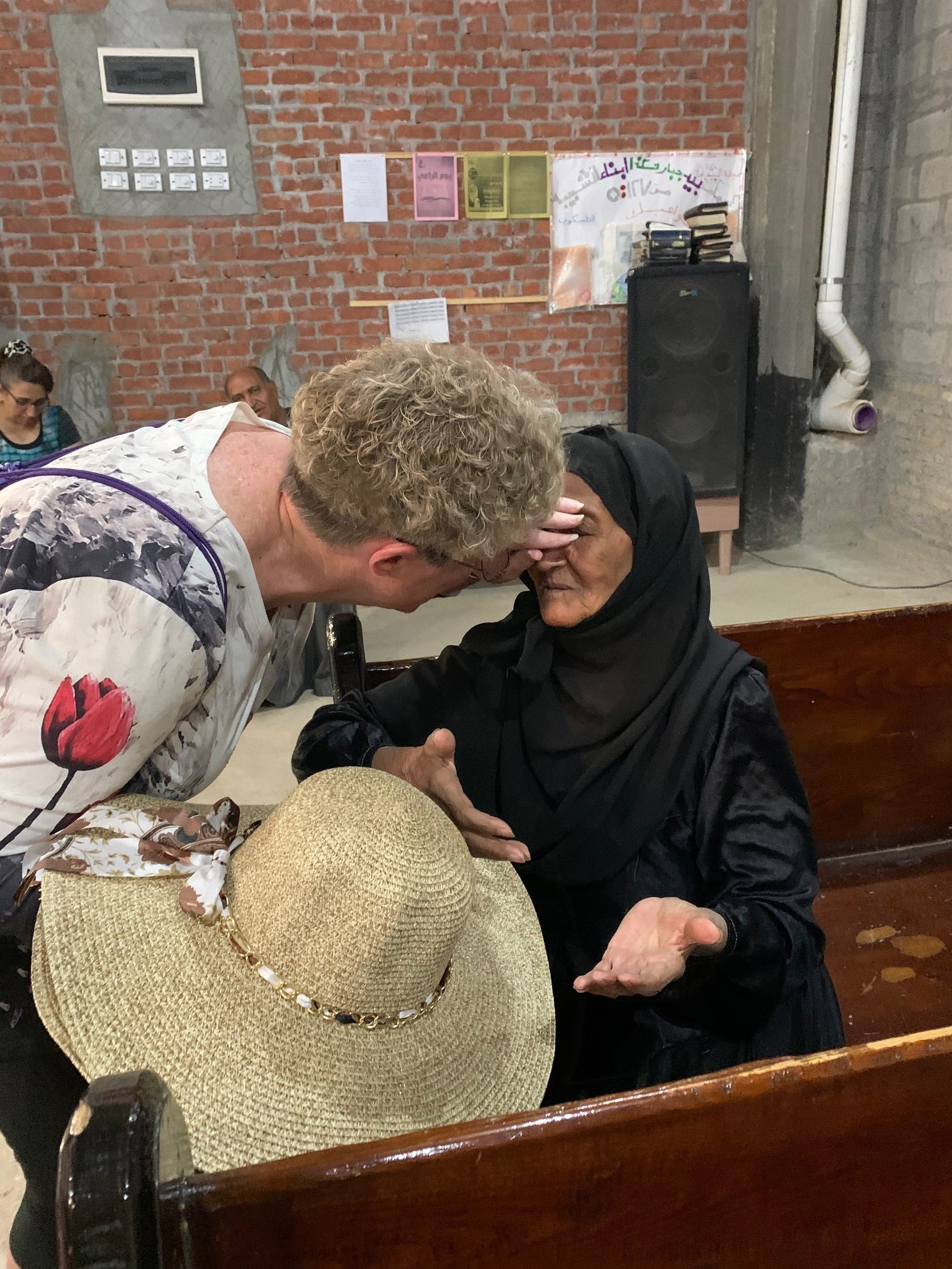 Peggy Shirley prays over an elderly member of the congregation whose eyesight is failing