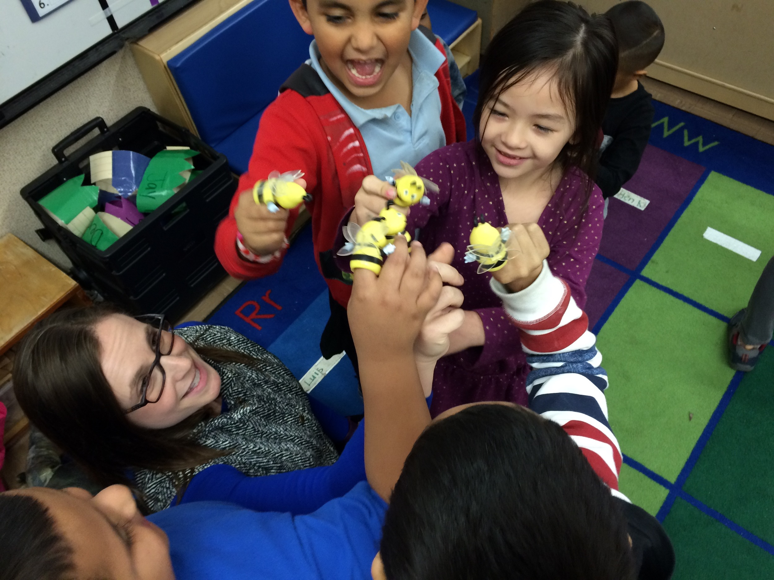 Teaching Artist Hannah Dworkin and the Story Explorers act out a scene with bee puppets.
