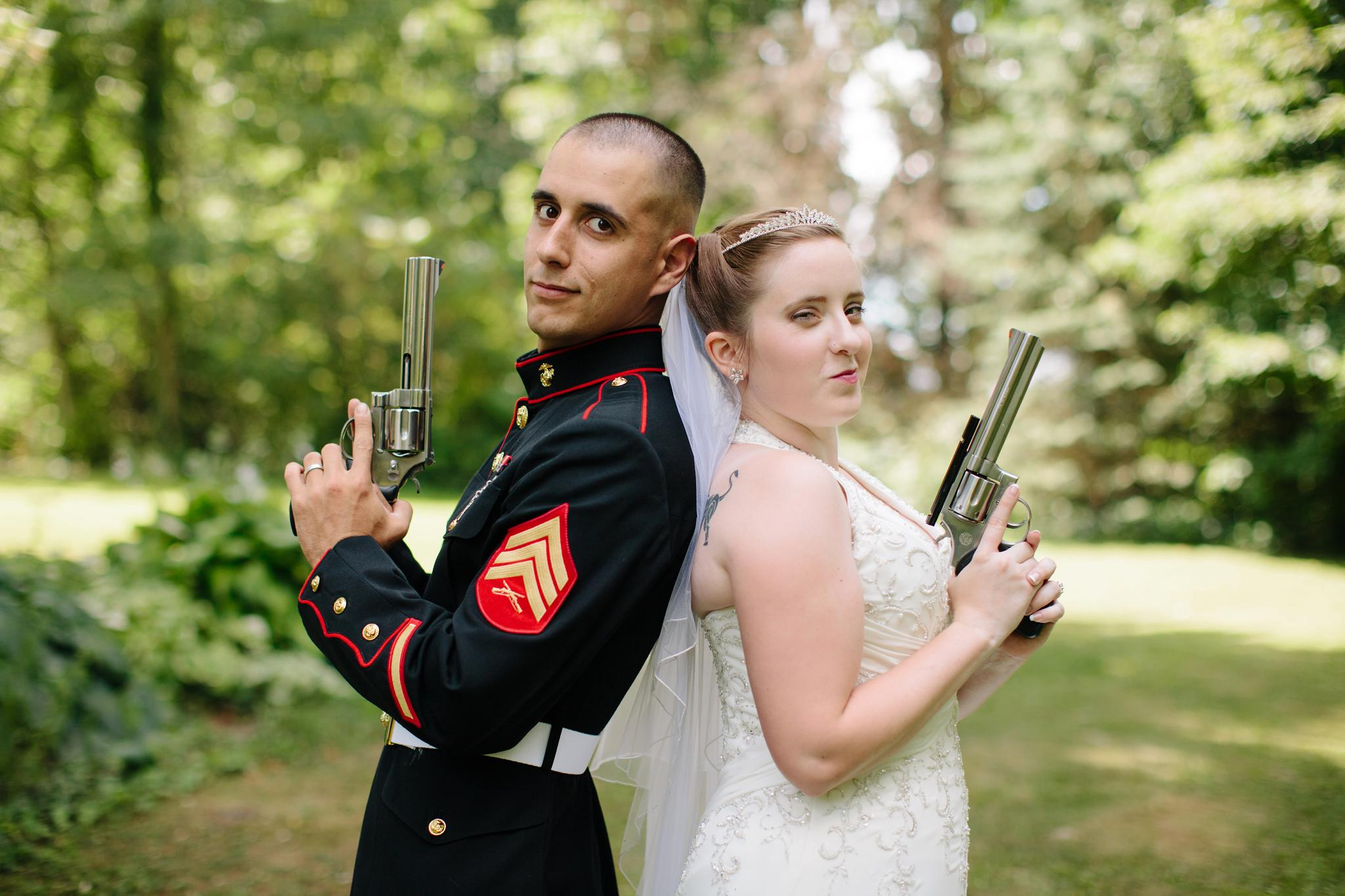 Bride and groom holding guns at their military wedding at Dotti Lou Grove in Tunkhannock PA.