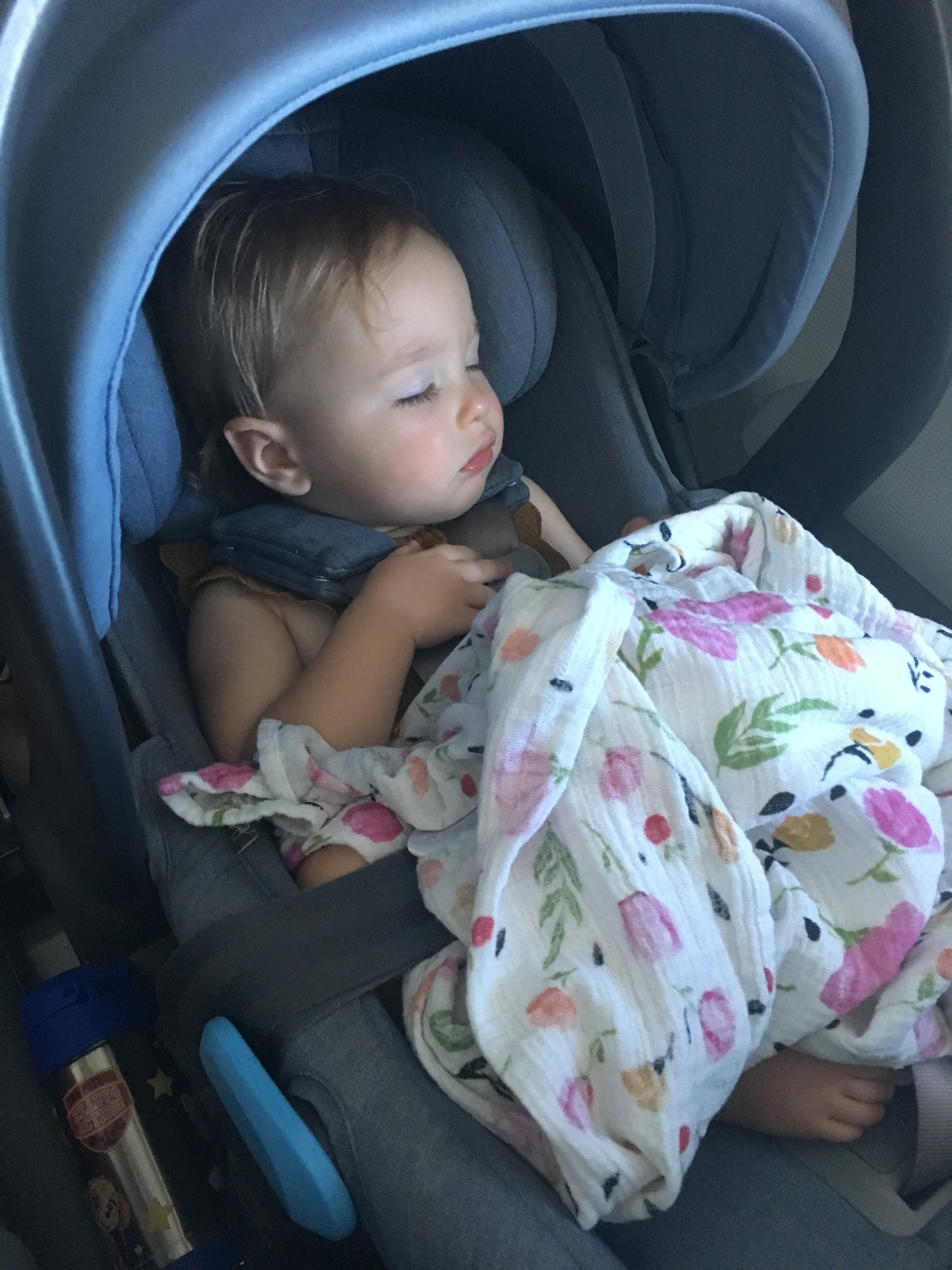 My older infant sleeping the flight away in her car seat.