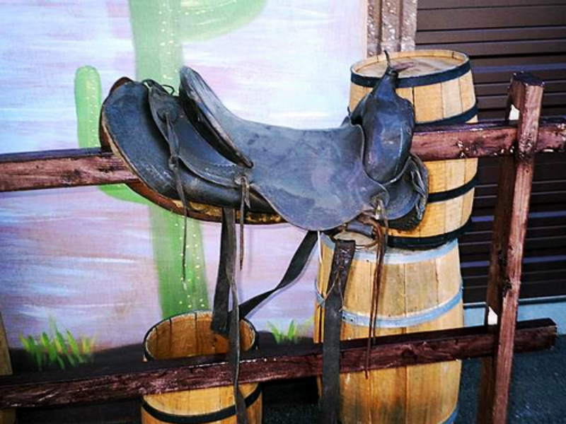 Assorted Western Props:  Wooden Barrels, Hitching Posts, Saddle Blankets and Horse Saddle