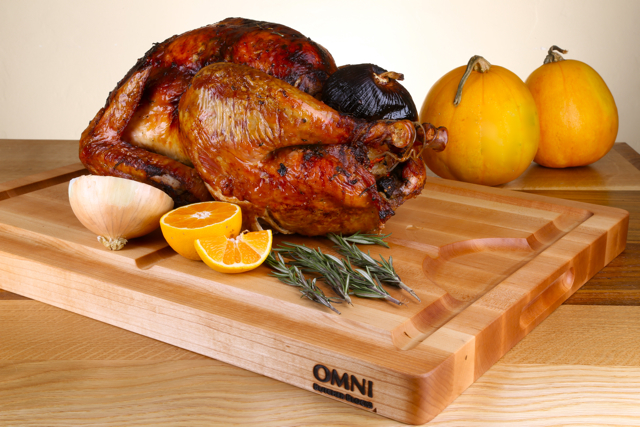 """The perfect carving board just in time for the holidays! Present your holiday meal on this beautifully crafted, Maple carving board for generations to come! Our unique and extra wide channels were specifically designed for carving and serving. The reverse side of the board is perfectly flat for everyday use. Approximate measurements are 22"""" x 16"""" x 1.5. $165.00 plus applicable taxes and shipping."""