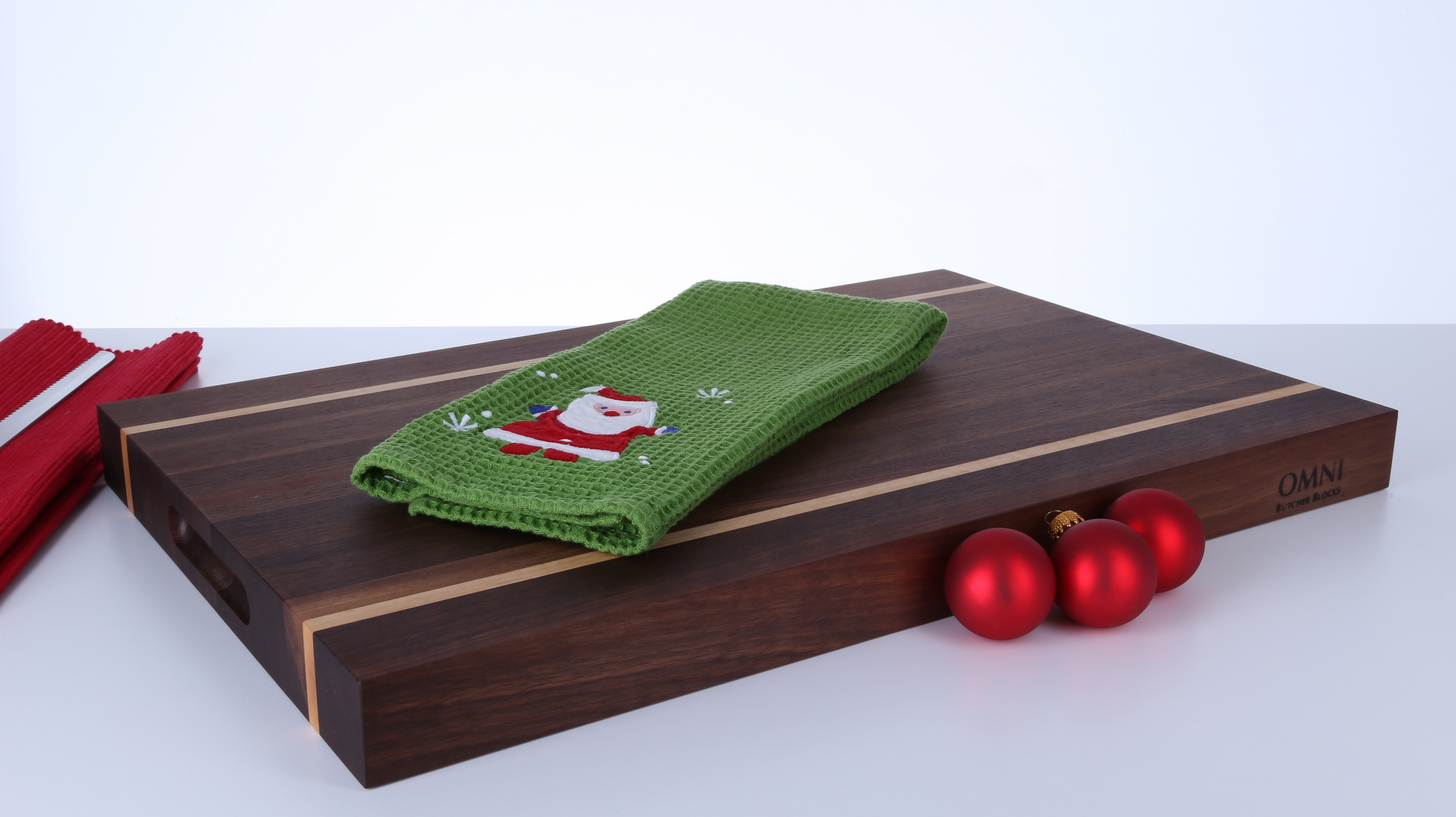 """Beautify your holiday table with this gorgeous Black Walnut Serving Board. Hard Sugar Maple accent strips provide a stunning contrast to the rich, chocolate hues of the Walnut.  Approximate size 20"""" x 14"""" x 1.5"""" with cut out handles for easy lifting. $165.00 plus applicable taxes and shipping."""