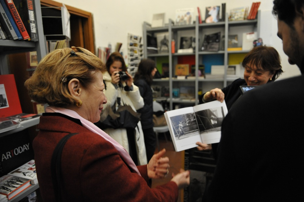 Curator Maria Paola Fornasiero showing exhibition catalog to Nina Rosenblum