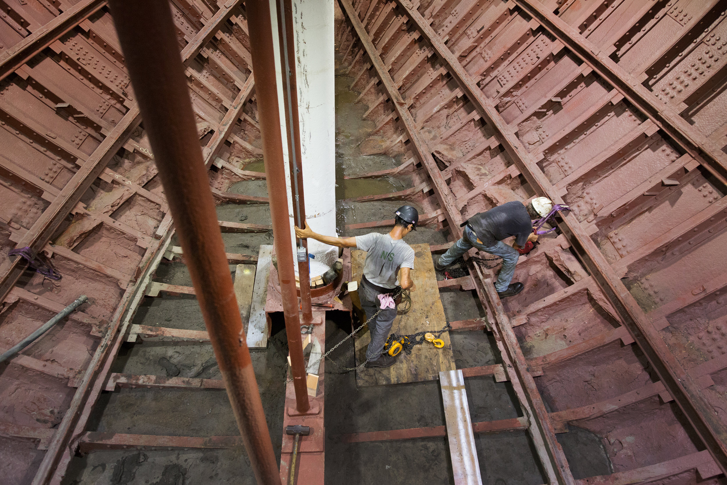 Riggers installing a mast at the hull of the Wavertree, a cargo sailing ship built in 1885. The ship belongs to the Seaport Museum and is undergoing a restoration at Caddell Dry Dock on Staten Island.