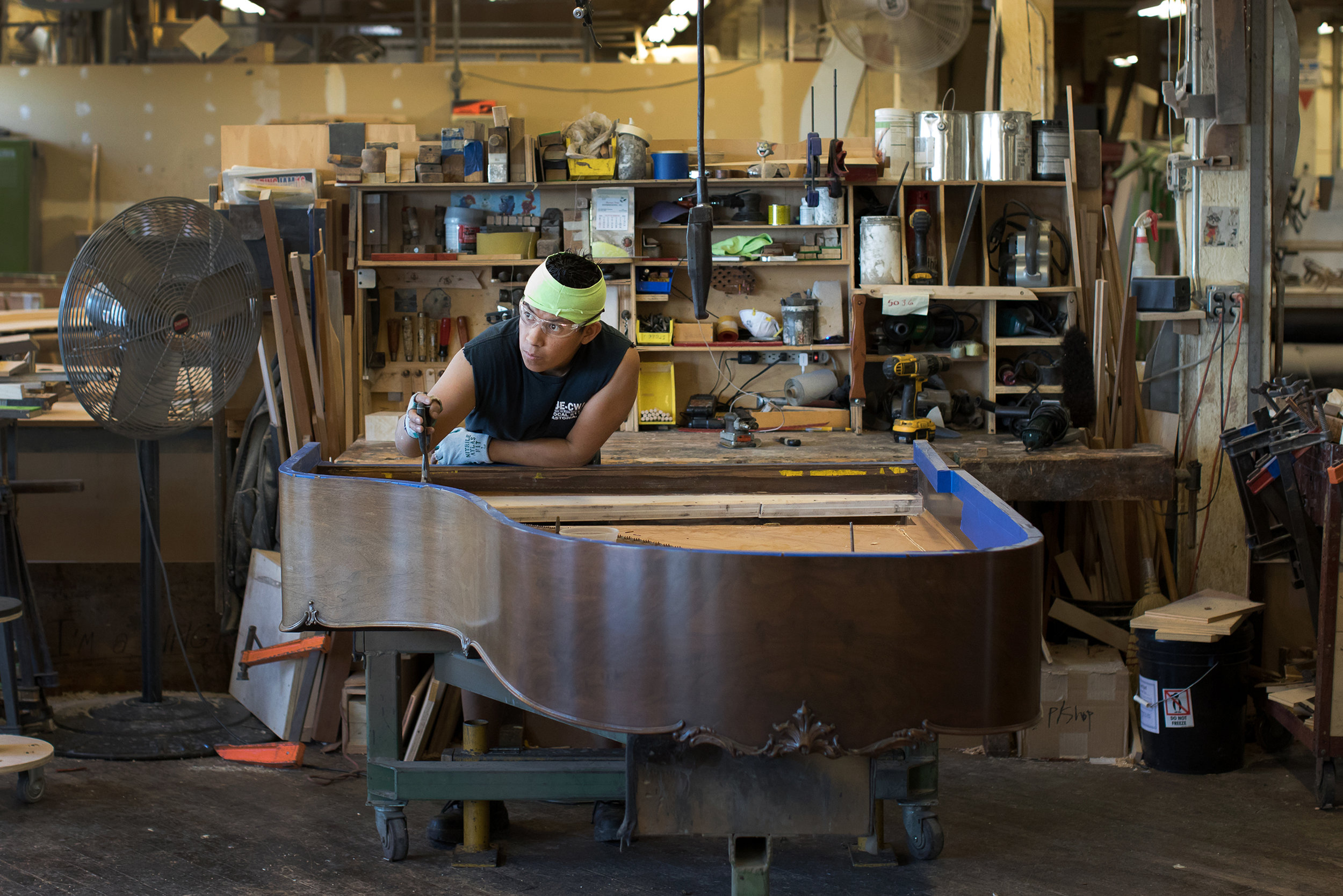 A worker preparing an old piano for restoration at Steinway and Sons in Queens.