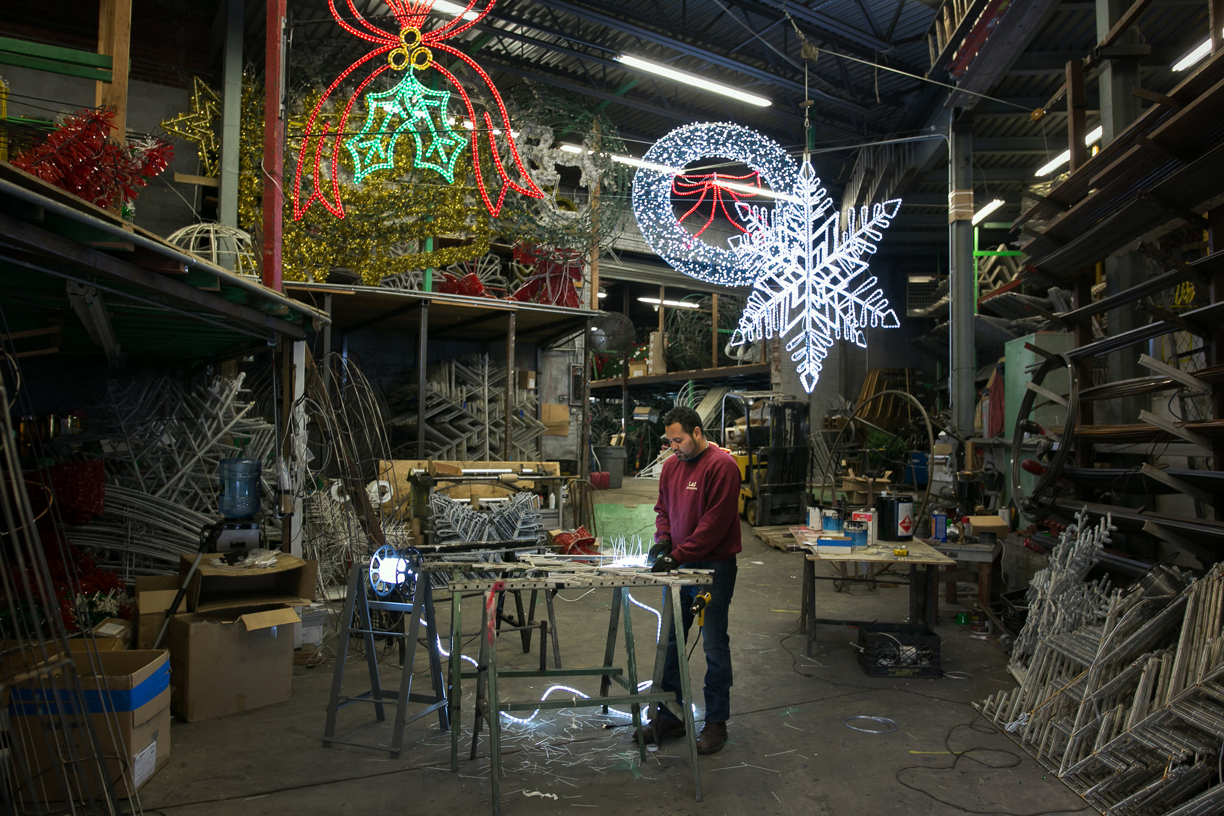Juan Midence assembling string lights around a holiday decoration at Illuminations by Arnold, a family-run business in Brooklyn.