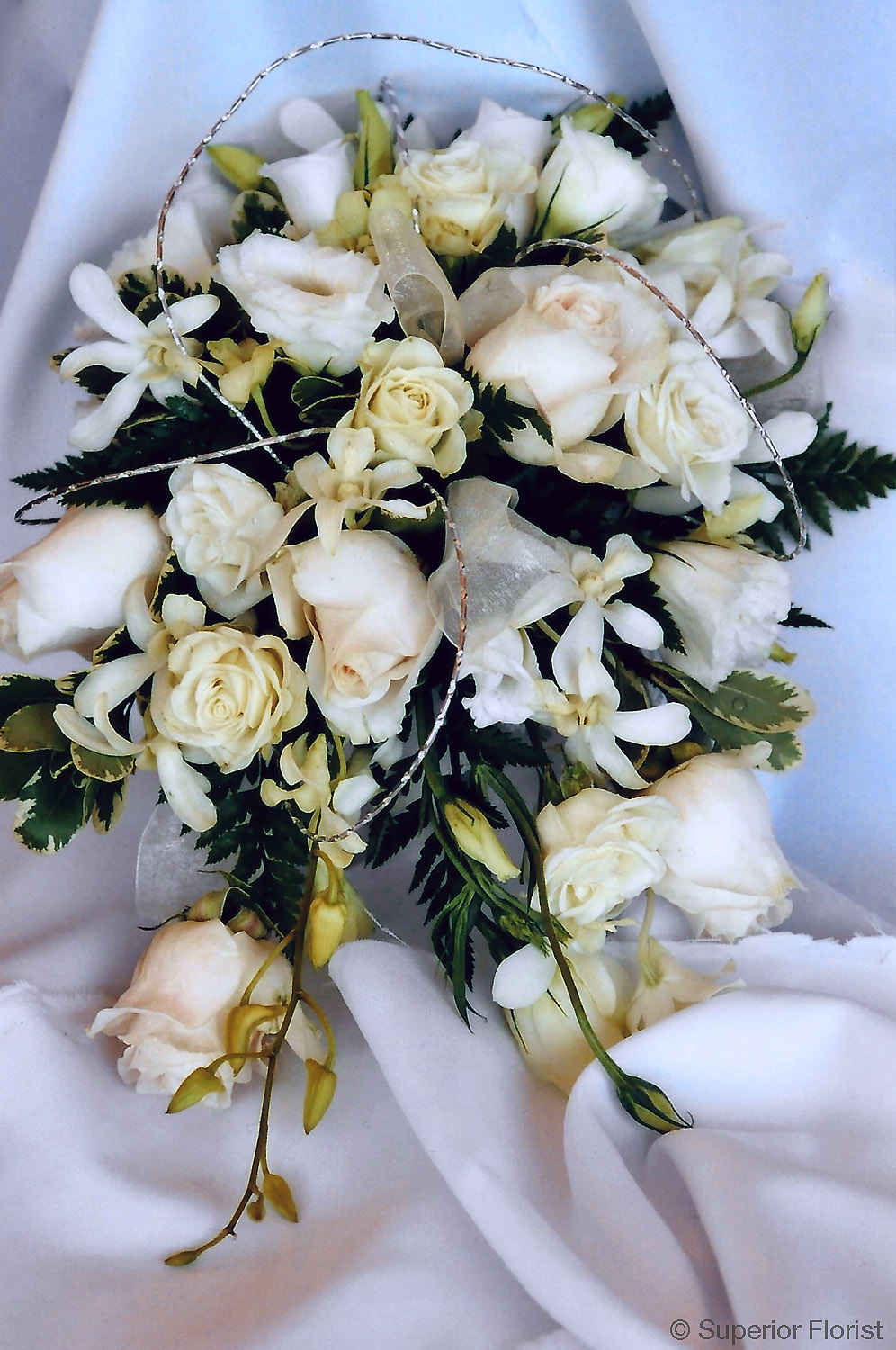 Superior Florist – Weddings – Personal Flowers: Teardrop bouquet of Lisianthus roses, Dendrobium and accents of metallic wisps.