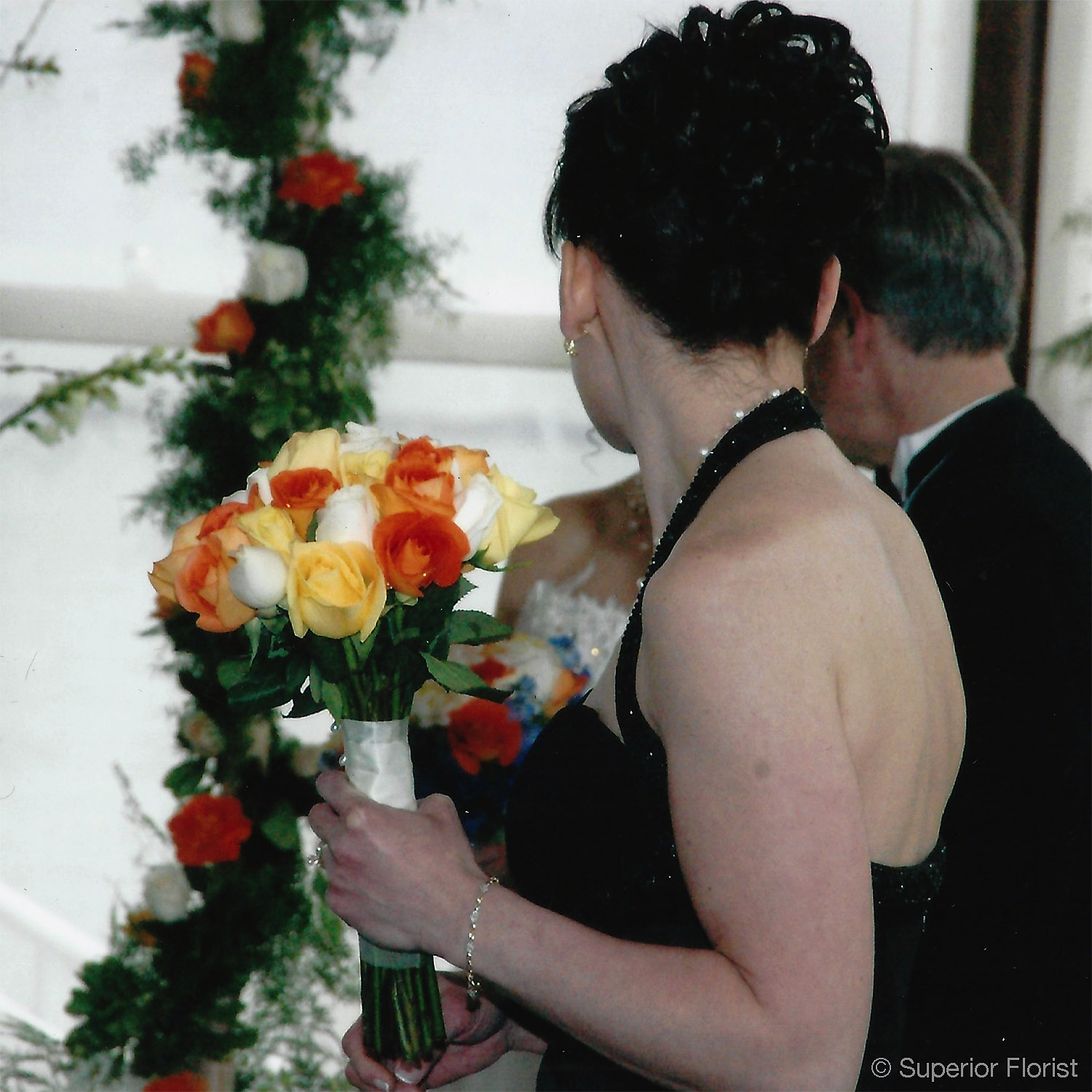 Superior Florist – Weddings – Personal Flowers: Simple, hand tied bridal bouquet of multi-colored roses.