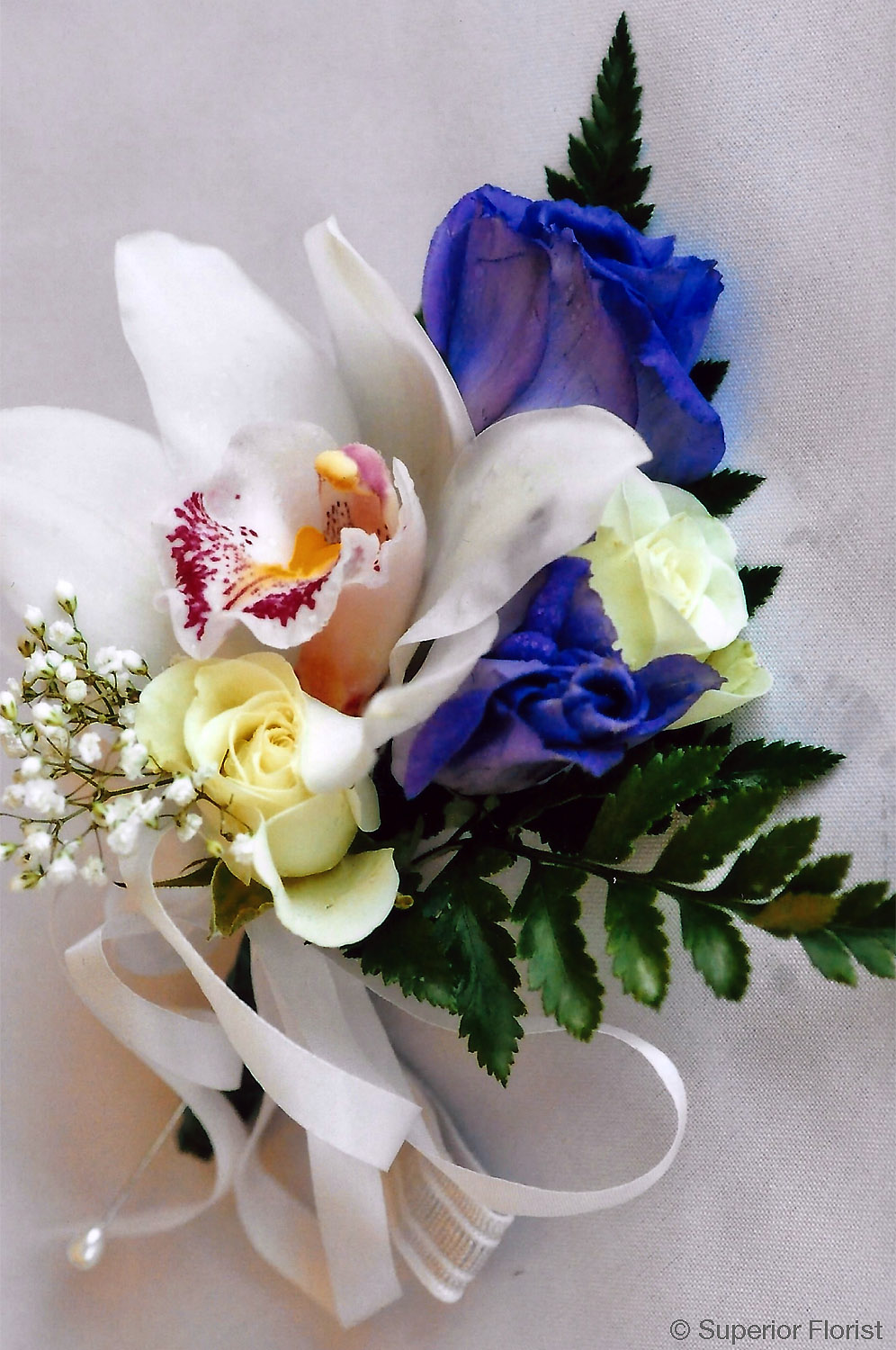 Superior Florist – Weddings – Personal Flowers: Corsage of a Cymbidium orchid, Lisianthus, two ivory roses, baby's-breath and greens.