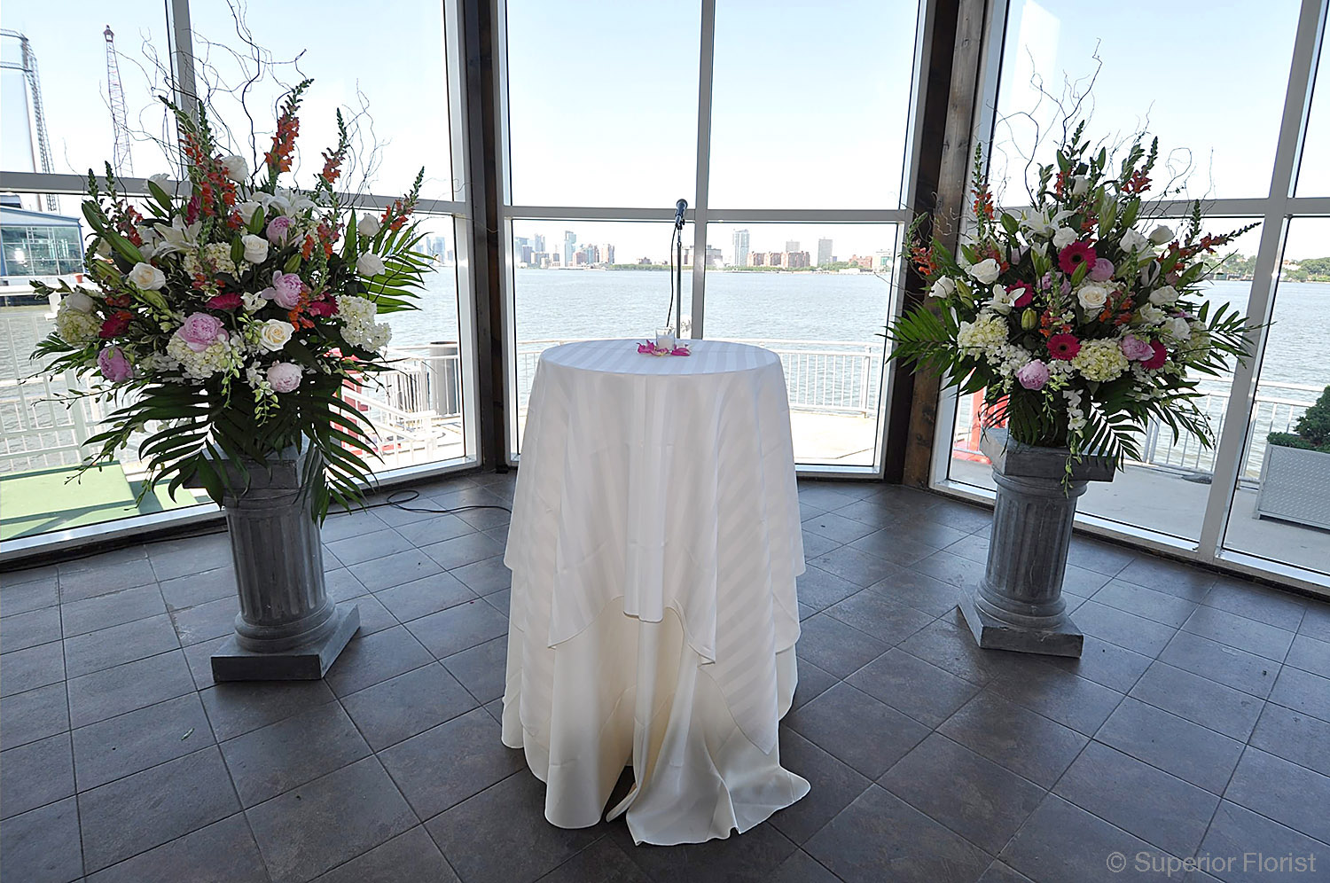 Superior Florist – Wedding Ceremony: Set of two matching floral baskets on pedestals flanking ceremonial table.