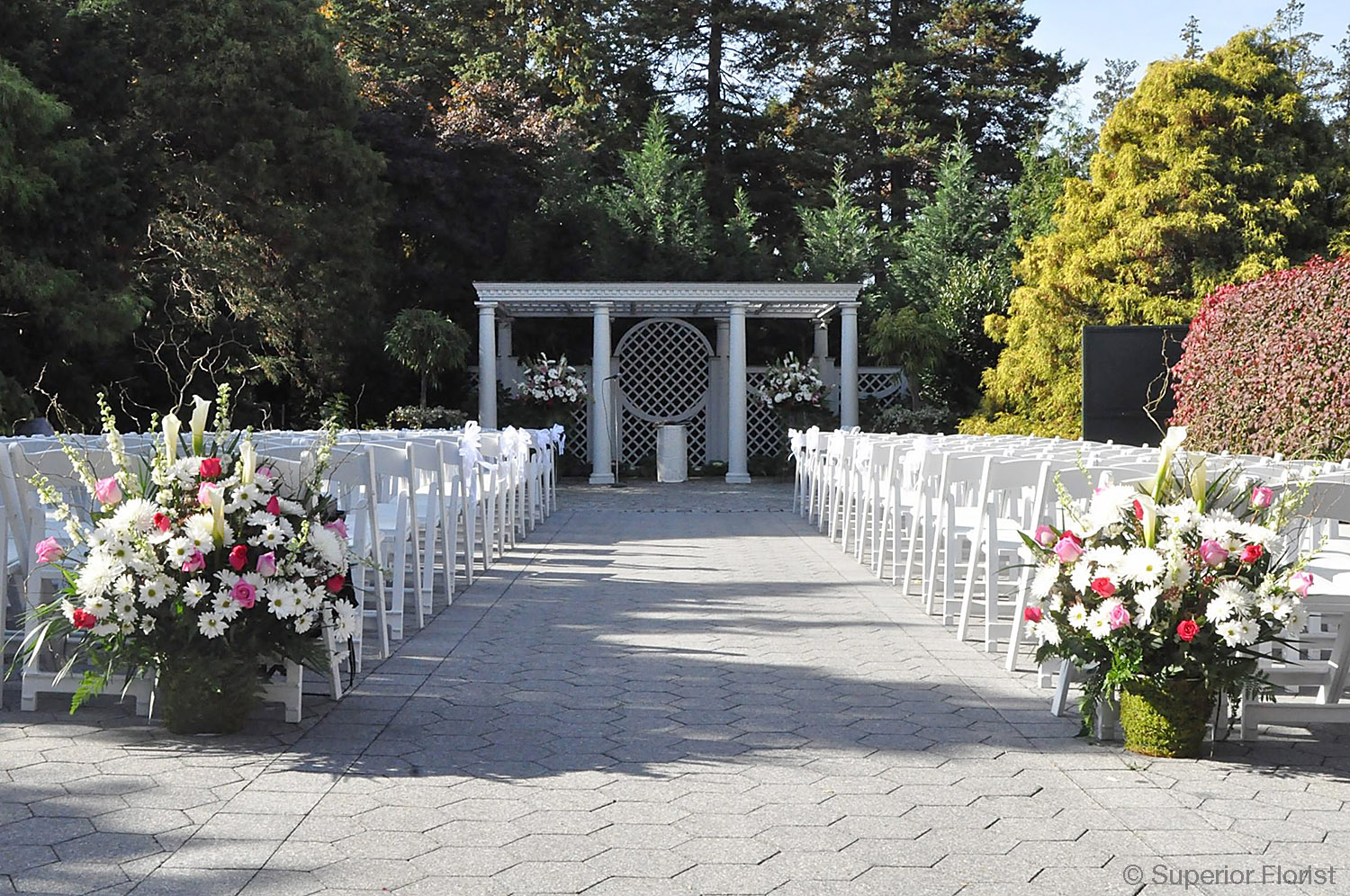 Superior Florist – Wedding Ceremony: Spring wedding ceremony outdoors at The New York Botanical Garden. Matching floral baskets in the foreground. Matching floral baskets under the gazebo in the background.