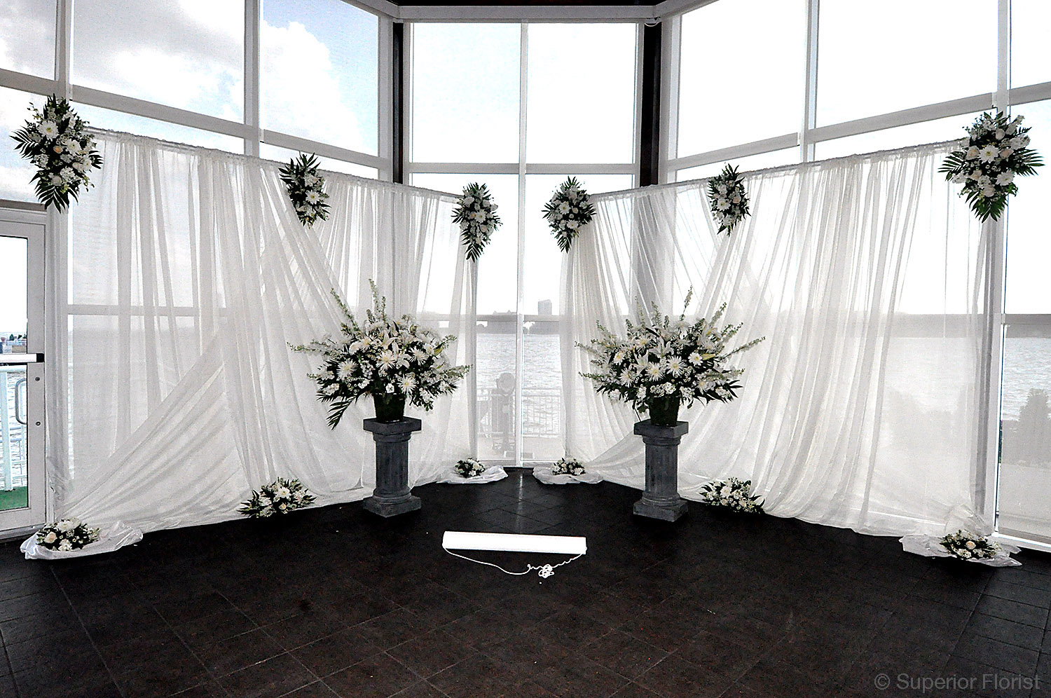 Superior Florist – Wedding Ceremony: Cluster and teardrop arrangements above and below. Two matching floral arrangements on pedestals. Ceremonial area with two freestanding panels of sheer fabric.