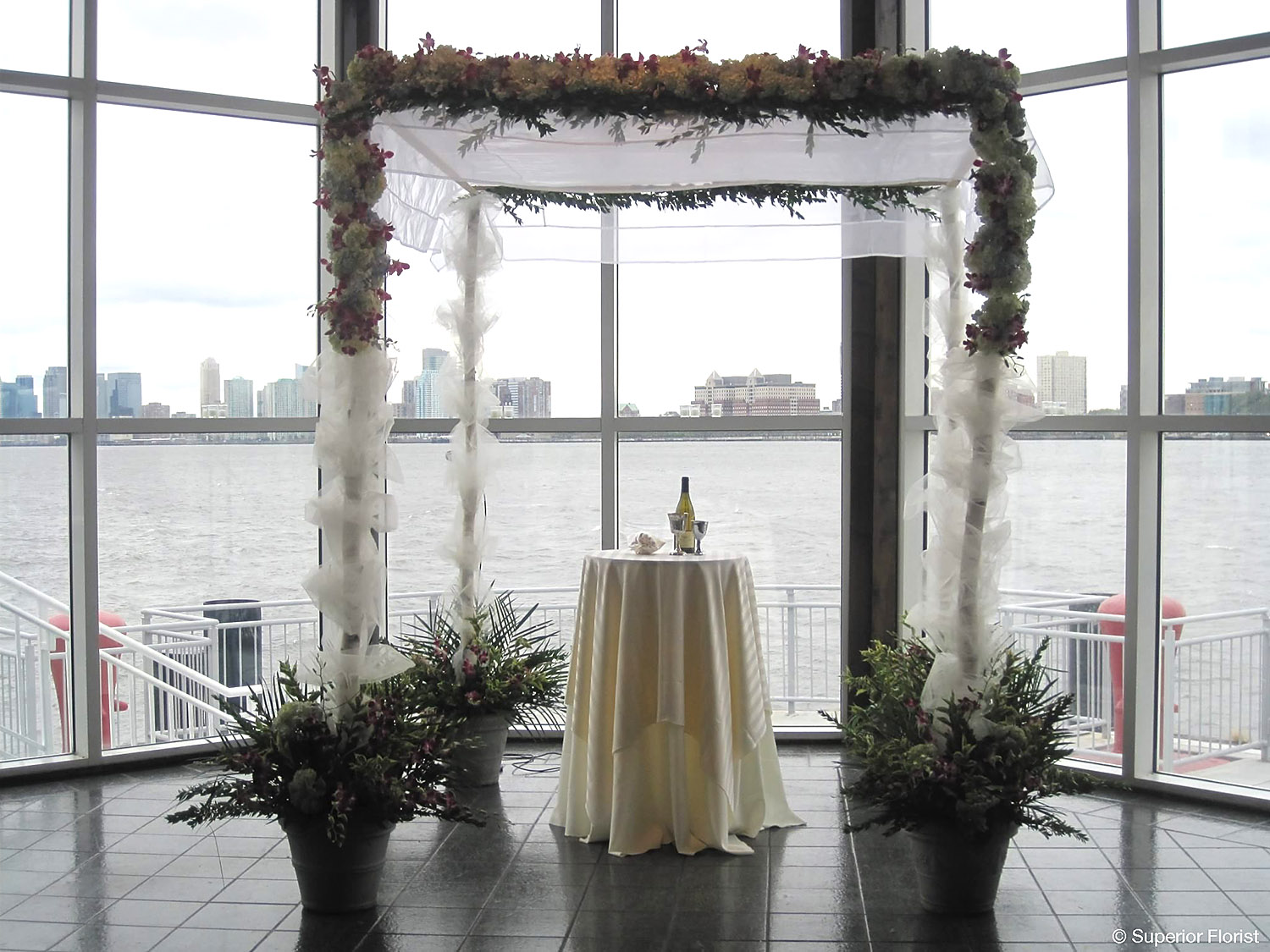 Superior Florist – Wedding Ceremony: Birch pole chuppah with white tulle fabric, garland of Hydrangea and Dendrobiums orchids. Complementing flowers at each base.