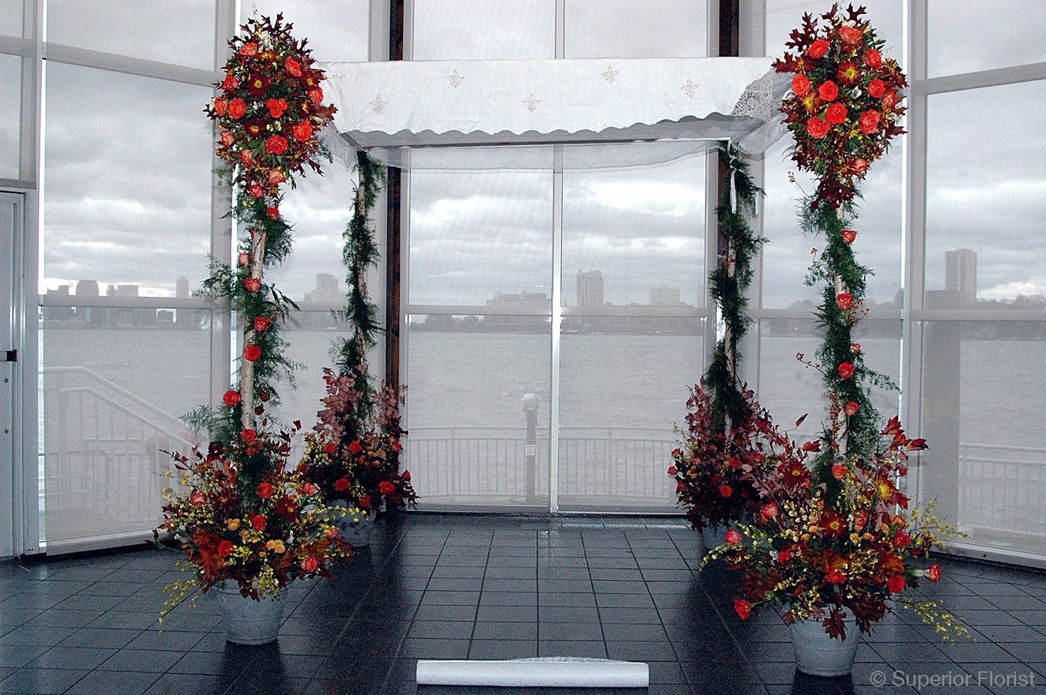 Superior Florist – Wedding Ceremony: Birch pole chuppah with family's personal chuppah top. Garland of greenery on poles, assortment of autumn flowers. The Lighthouse at Chelsea Piers, NYC.