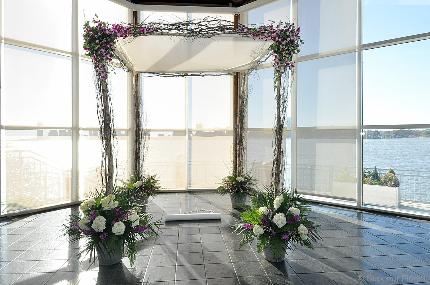 Superior Florist – Wedding Ceremony: Birch pole chuppah with white satin top. Natural birch branches on poles and beams. Teardrop arrangements of variegated Dendrobium orchids. Bases in white and purple.