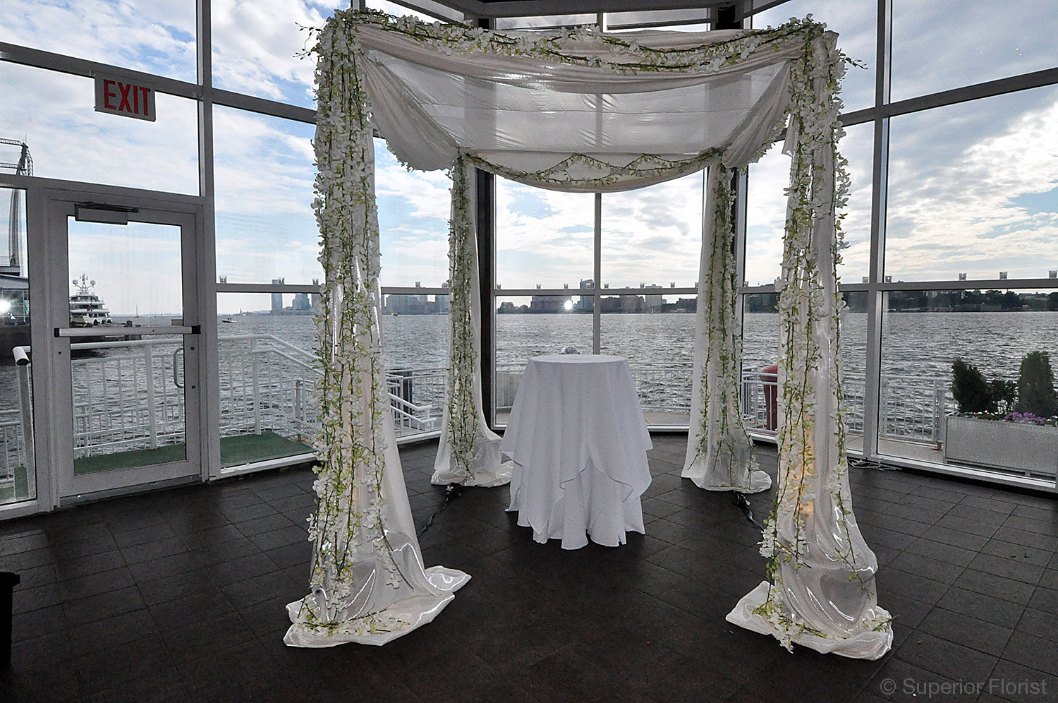 Superior Florist – Wedding Ceremony: Chuppah draped in white, bridal satin fabric. White Dendrobium orchids outline chuppah frame. Up-lighting from within the chuppah poles.