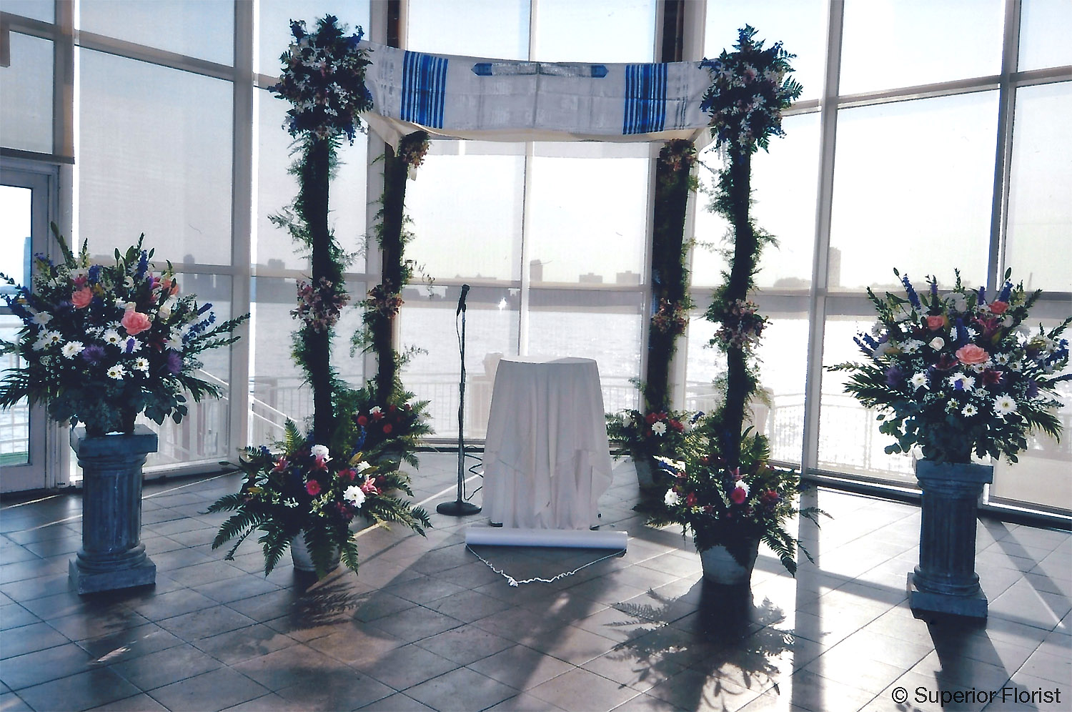 Superior Florist – Wedding Ceremony: Birch pole chuppah with family tallis on top. Flanked by two matching basket arrangements on pedestals.